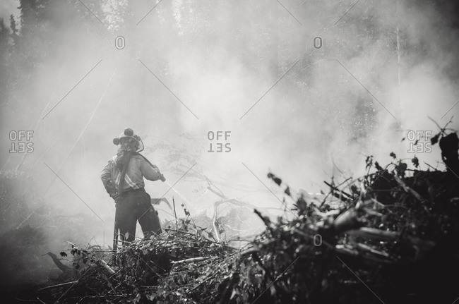 Alberta, British Colombia, Canada - July 13, 2015: Black and white of Panorama Crew Services member hosing smoking fallen trees, Alberta, British Colombia, Canada