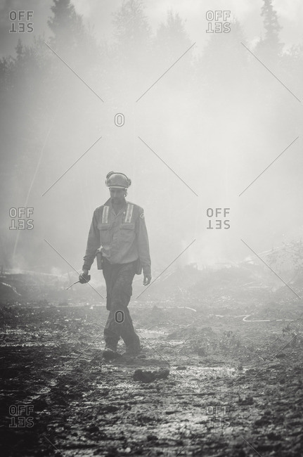 Alberta, British Colombia, Canada - July 13, 2015: Black and white of Panorama Crew Services member walking through forest fire remains, Alberta, British Colombia, Canada