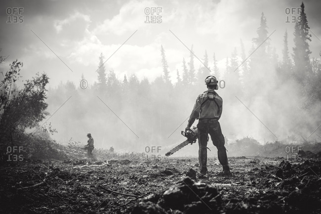 Alberta, British Colombia, Canada - July 13, 2015: Black and white of Panorama Crew Services members with chainsaws, Alberta, British Colombia, Canada