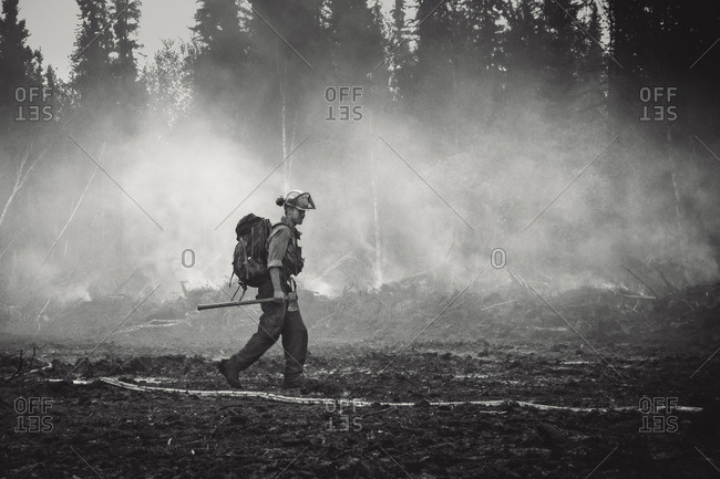 Alberta, British Colombia, Canada - July 13, 2015: Member of Panorama Crew Services walking remains after forest fire carrying axe, Alberta, British Colombia, Canada