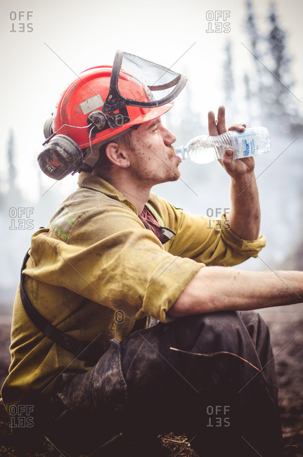 Alberta, British Colombia, Canada - July 13, 2015: Member of Panorama Crew Services taking a drink of water, Alberta, British Colombia, Canada