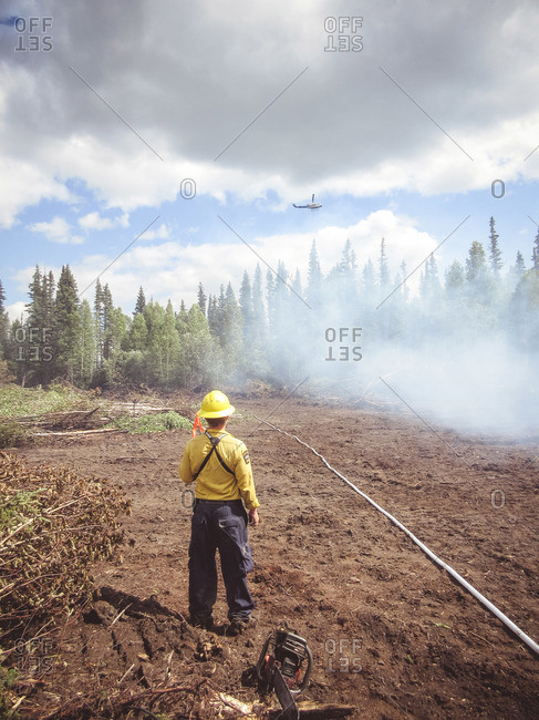 Alberta, British Colombia, Canada - July 13, 2015: Member of Panorama Crew Services watching as helicopter drops water over forest fire, Alberta, British Colombia, Canada
