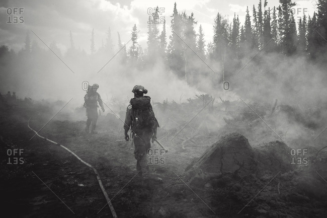 Alberta, British Colombia, Canada - July 13, 2015: Black and white of Member of Panorama Crew Services members walking through smoke, Alberta, British Colombia, Canada