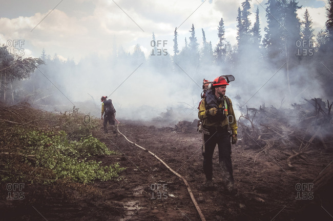 Alberta, British Colombia, Canada - July 13, 2015: Two members of Panorama Crew Services walking through remains of fire with hose, Alberta, British Colombia, Canada