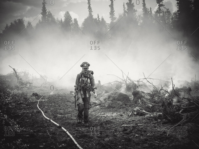 Alberta, British Colombia, Canada - July 13, 2015: Black and white of Member of Panorama Crew Services member walking out of the smoke, Alberta, British Colombia, Canada