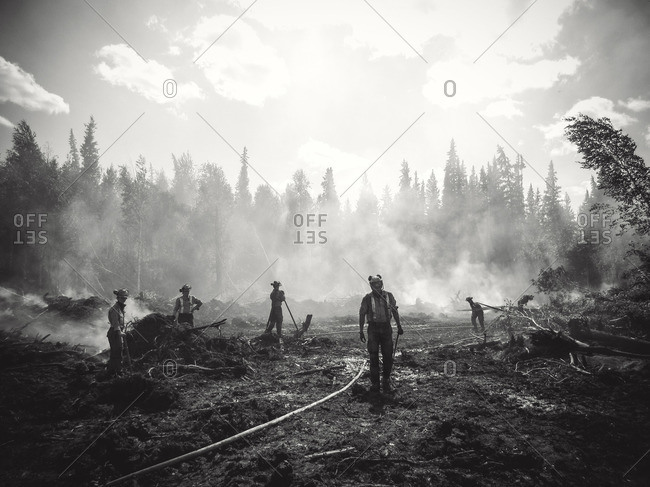 Alberta, British Colombia, Canada - July 13, 2015: Black and white members of Panorama Crew Services cleaning up forest fire remains, Alberta, British Colombia, Canada