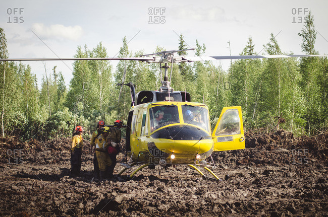 Alberta, British Colombia, Canada - July 13, 2015: Members of Panorama Crew Services getting out of helicopter, Alberta, British Colombia, Canada
