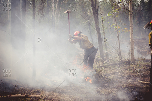 Alberta, British Colombia, Canada - July 16, 2015: Female member of Panorama Crew Services chopping flaming brush with axe, Alberta, British Colombia, Canada
