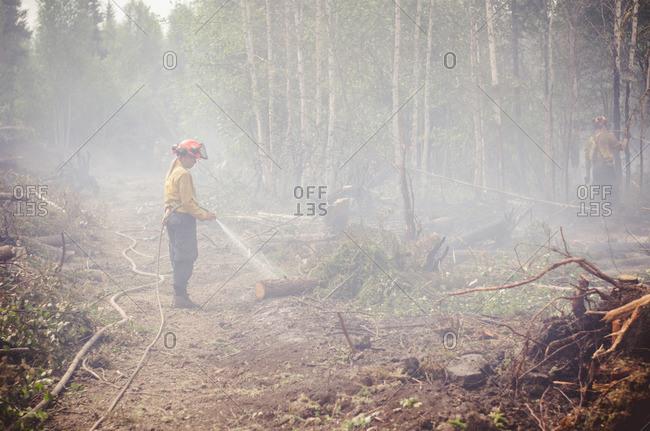 Alberta, British Colombia, Canada - July 16, 2015: Member of Panorama Crew Services hosing down smoking trees, Alberta, British Colombia, Canada