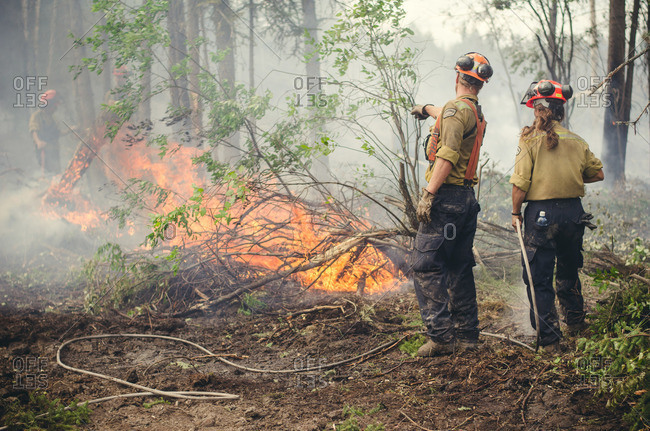 Alberta, British Colombia, Canada - July 16, 2015: Members of Panorama Crew Services pointing to flames, Alberta, British Colombia, Canada