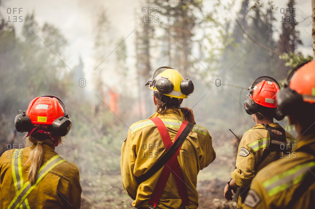 Alberta, British Colombia, Canada - July 16, 2015: Members of Panorama Crew Services watching flames, Alberta, British Colombia, Canada