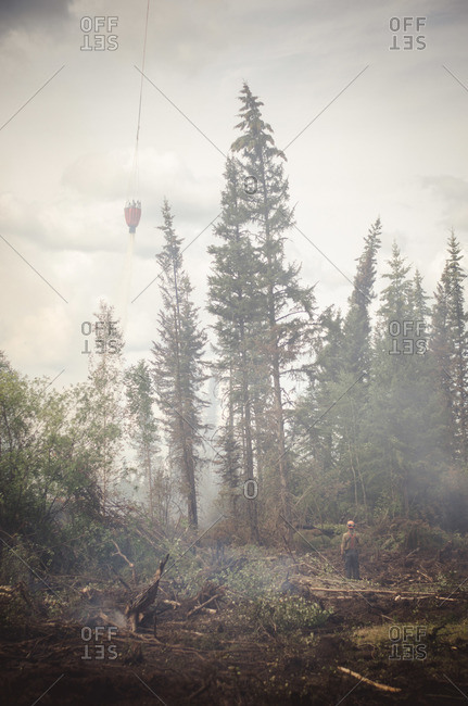 Alberta, British Colombia, Canada - July 16, 2015: Helicopter bucket dropping water with Panorama Crew Services member standing on the ground, Alberta, British Colombia, Canada