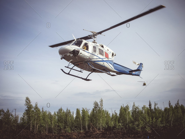 Alberta, British Colombia, Canada - July 16, 2015: Two helicopters flying over burnt down forest, Alberta, British Colombia, Canada