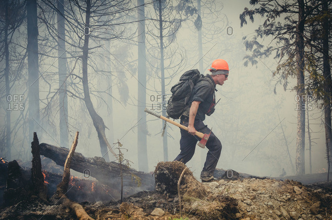 Alberta, British Colombia, Canada - July 27, 2015: Side view of members of Panorama Crew Services walking over remains while carrying axe, British Colombia, Canada
