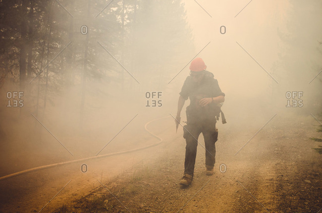 Alberta, British Colombia, Canada - July 27, 2015: Panorama Crew Services member walking through smoke, British Colombia, Canada