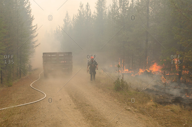 Alberta, British Colombia, Canada - July 27, 2015: Panorama Crew Services member walks away from truck as trees are in flames, British Colombia, Canada