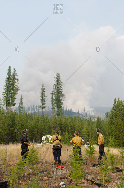 Alberta, British Colombia, Canada - July 27, 2015: Members of Panorama Crew Services standing in field watching smoke fill the sky, British Colombia, Canada