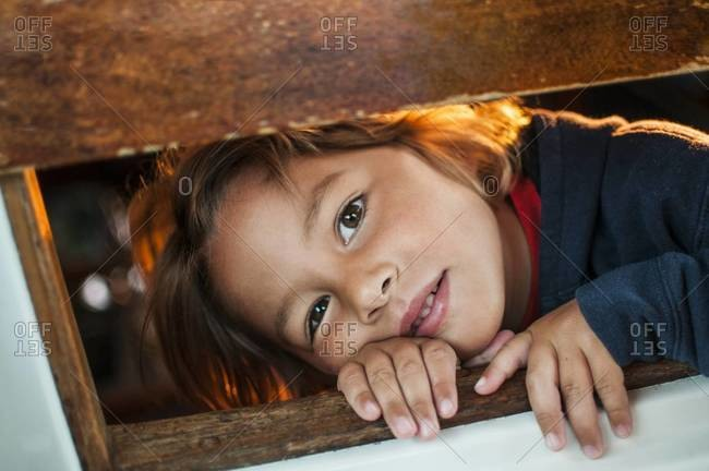 Young boy peeking through a window on sailboat