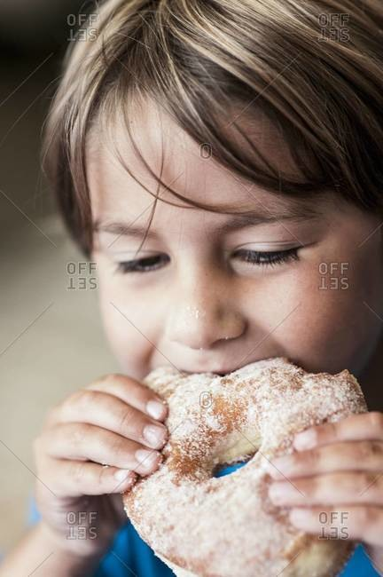 Young boy biting into a sugary donut