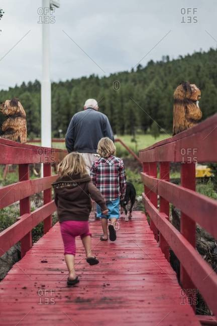 Back view of children following grandfather and dog across red wooden bridge
