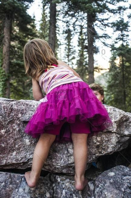 Back view of young girl in pink tulle skirt climbing a rock wall in bare feet