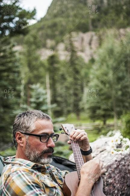 Bearded man playing ukulele in mountain landscape