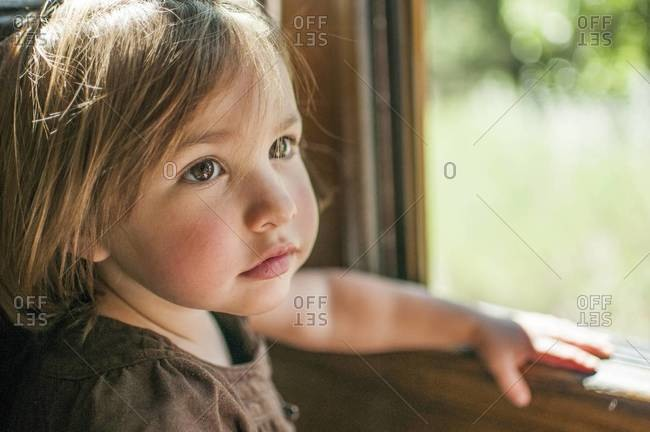 Toddler girl standing at window
