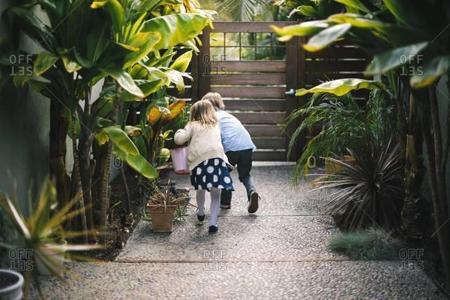Two children hunting for Easter eggs in garden