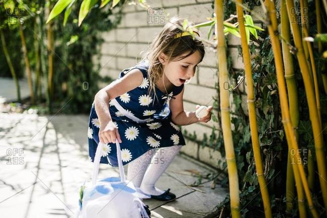 Girl finding Easter egg in bamboo in tropical garden