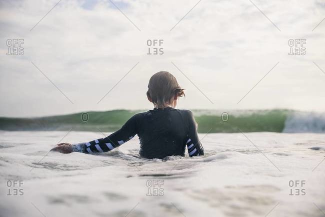 Back view of boy in wetsuit facing incoming wave