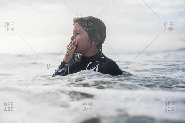 Young boy in wetsuit swimming in ocean