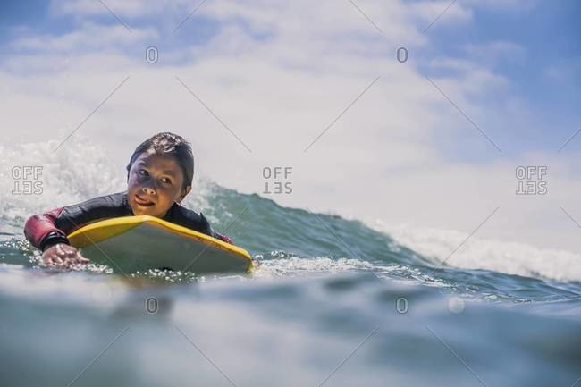 Boogie boarding young boy riding incoming wave