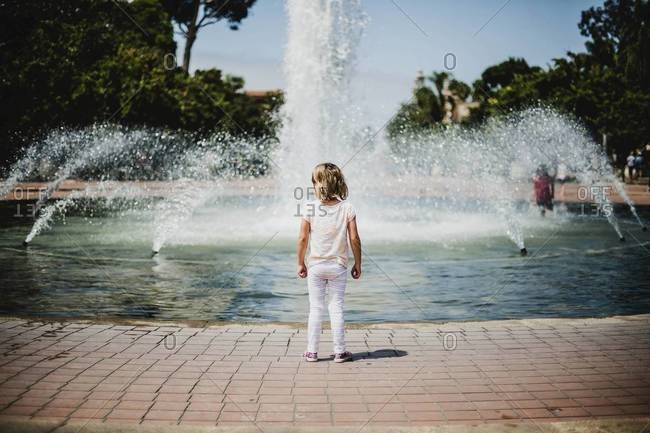 Back view of young girl standing at fountain