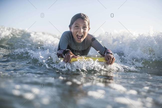 Exhilarated young boy riding wave on boogie board