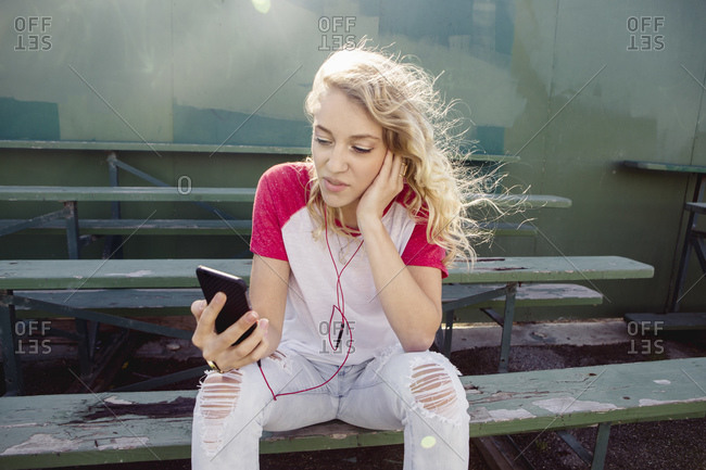 Teen girl in ripped jeans sits on bleachers and listens to her music player