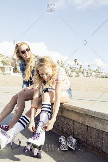 Young woman sits on wall at beach while her friend laces up a pair of roller skates