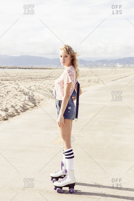 Young woman in roller-skates on beach path