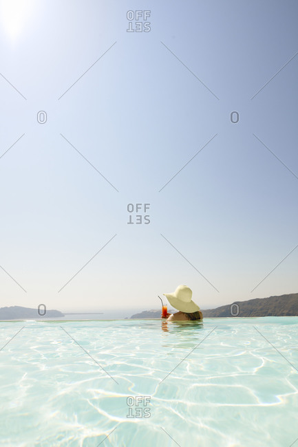 Woman with cocktail in swimming-pool, Greece