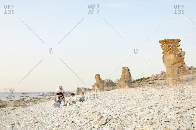 Family on beach, rock formations on background, Gotland