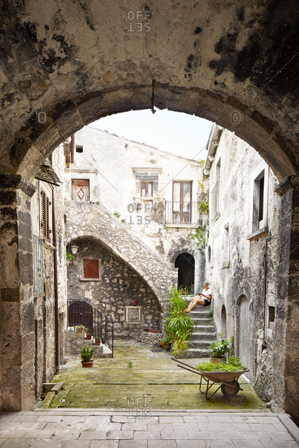 Woman sitting on steps of old building, Italy