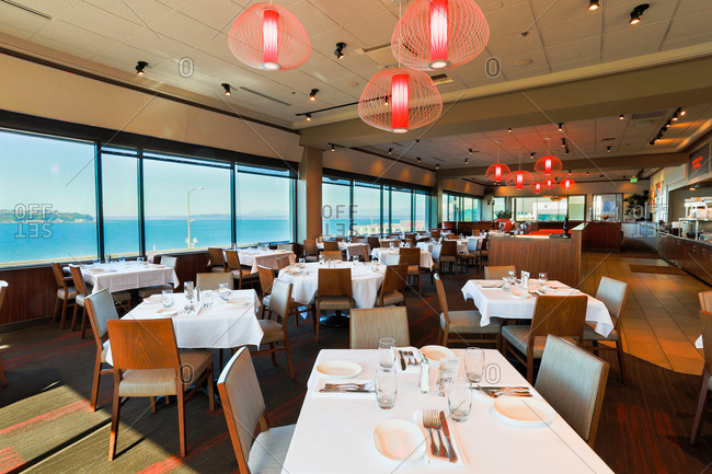 Seattle, WA - August 20, 2013: Upscale seafood restaurant dining room oversees ocean in Seattle, Washington