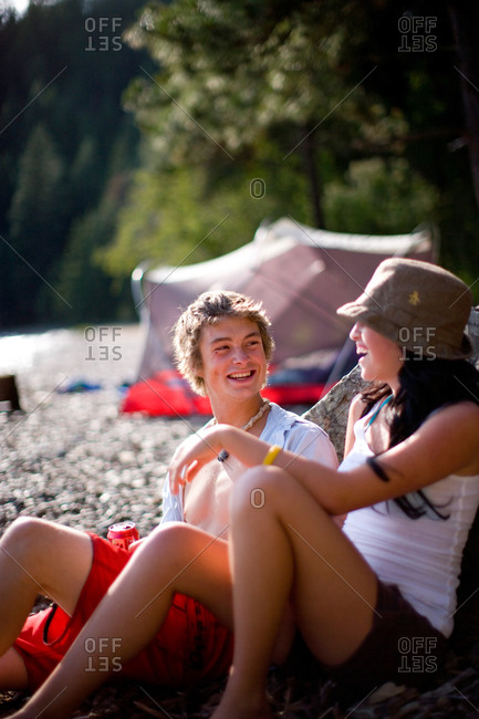 Friends camping and hanging out while camping along shore of Lake Pend Oreille, Idaho
