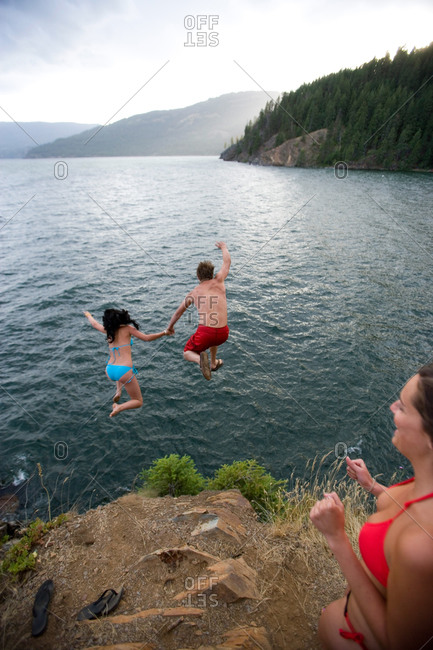 Two people jumping into lake as one woman watches