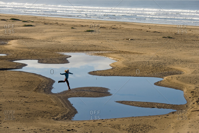 Woman jumping over tidal ponds at beach