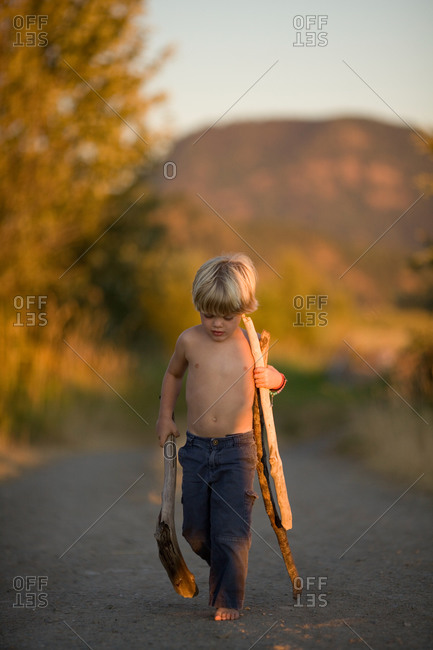 A little boy walking a dirt road in the late summer