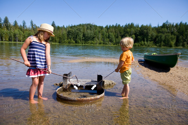 A young boy and girl attempting to roast marshmallows over a watery fire pit