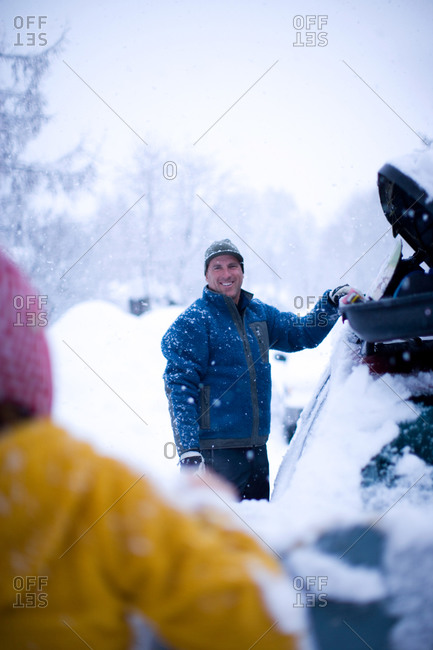 Wintertime lifestyle portrait of an adult man unloading gear from the top of his car