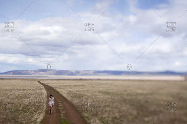 Woman riding a bike on a desolate dirt road under a cloudy sky
