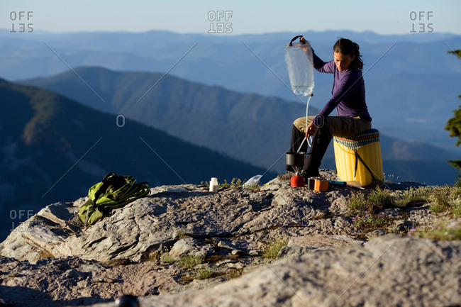 A woman dispensing water into a pot high up in the mountains