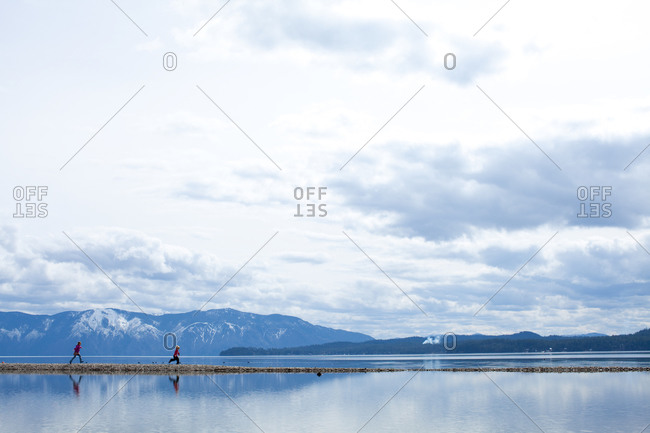 Two children running on a thin strip of land in the middle of a big mountain lake
